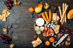 Los aperitivos presentan con bocados italianos de los antipasti La variedad del queso y del charcuterie sube sobre fondo de mader imagen de archivo
