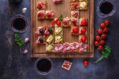 Los aperitivos presentan con bocados y vino italianos de los antipasti en vidrios Brushetta o los tapas españoles tradicionales a imagen de archivo libre de regalías