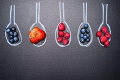 Los arándanos, fresas, frambuesas, y una variedad de bayas, en cucharas pintadas de la tiza, ponen el texto, visión superior Imagen de archivo libre de regalías