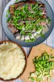 Los arenques cortan con las cebollas verdes con los purés de patata foto de archivo libre de regalías