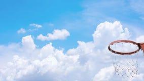 Los aros y las redes de baloncesto que sacud?an la bola cayeron el cielo del fondo con las nubes y el sol en verano almacen de video