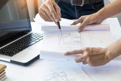 Los arquitectos dirigen la discusión en la tabla con el modelo - clo Imagenes de archivo