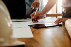 Los arquitectos dirigen la discusión en la tabla con el modelo - clo Imagen de archivo