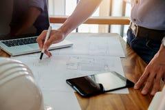 Los arquitectos dirigen la discusión en la tabla con el modelo - clo Fotos de archivo libres de regalías