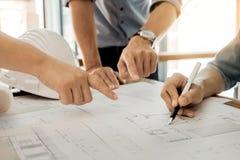 Los arquitectos dirigen la discusión en la tabla con el modelo - clo Fotografía de archivo libre de regalías
