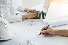 Los arquitectos dirigen la discusión en la tabla con el modelo - clo Imágenes de archivo libres de regalías