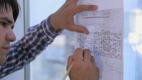 Los arquitectos irreconocibles dan el trabajo con el bosquejo, dibujo, planean cerca de ventana panorámica de la oficina limpia b metrajes