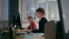Los arquitectos jovenes de los colegas están trabajando en la oficina en los ordenadores metrajes