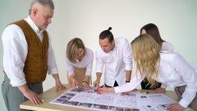 Los arquitectos modernos, los electricistas, o el diseñador, arquitecto, constructores discuten con su plan de trabajo del client almacen de video