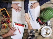 Los arquitectos y los técnicos jovenes analizan el proyecto de una casa residencial fotos de archivo libres de regalías