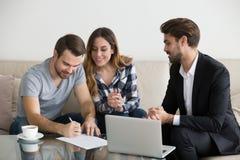 Los arrendatarios o los arrendatarios felices de los pares firman agente inmobiliario de alquiler de la reunión del contrato foto de archivo libre de regalías