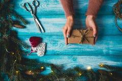 Los artículos de la Navidad en un azul wodden la tabla Manos del ` s de la mujer que envuelven el regalo de la Navidad Fotografía de archivo