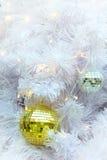 Los artículos de oro de la bola de la Navidad del espejo en la empanada blanca y el bokeh amarillo forman el fondo de la iluminac Imágenes de archivo libres de regalías