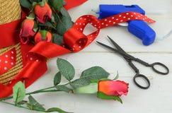 Los artículos para adornar un capo incluyen un sombrero de paja, rosas del tijera del vintage, de seda y un arma de pegamento foto de archivo