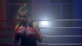 Los artes marciales, individuo del púgil en guantes de boxeo realizan soplos en el anillo durante practicar antes de primer de la almacen de metraje de vídeo