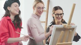 Los artistas de sexo femenino se colocan en el caballete y juntos dibujan una imagen almacen de video