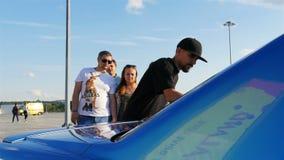 Los artistas en casquillo negro adornan el coche azul con los modelos