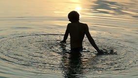 Los Arty sirven hacen un círculo grande alrededor de sí mismo en agua en la puesta del sol almacen de metraje de vídeo