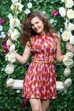 Los asimientos sonrientes de la mujer balancean overgrown con las flores fotografía de archivo