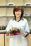 Los asimientos sonrientes de la mujer colorearon el pulimento de clavo imagen de archivo libre de regalías