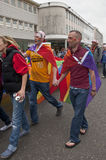 Los asistentes del festival sostienen las manos y la bandera del arco iris Imagenes de archivo