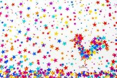 Los asteriscos multicolores dispersaron en un fondo blanco y la f Foto de archivo libre de regalías