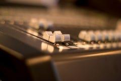 Los atenuadores audios del mezclador se cierran para arriba con el fondo borroso Fotografía de archivo libre de regalías