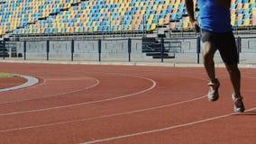 Los atletas útiles que corren alrededor del estadio, calentando muscles antes de entrenar metrajes
