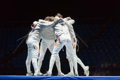 Los atletas abrazan en competencias en el campeonato del mundo en el cercado Fotografía de archivo
