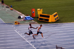 Los atletas compiten en la raza de relais 4x100 Fotos de archivo libres de regalías