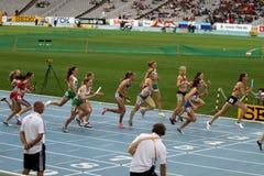 Los atletas compiten en la raza de relais 4x400 Imagenes de archivo