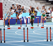 Los atletas compiten en los 400 contadores de la carrera de vallas Imagen de archivo libre de regalías