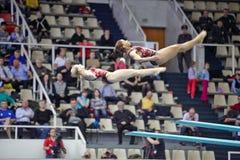 Los atletas de sexo femenino realizan ejercicio en el salto syncronized del trampolín Imagen de archivo