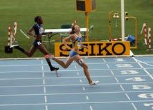 Los atletas en el final de 400 contadores compiten con Foto de archivo libre de regalías