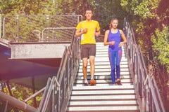Los atletas jovenes que corren abajo de los pasos de la ciudad parquean Foto de archivo libre de regalías