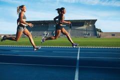 Los atletas llegan la meta en pista Foto de archivo libre de regalías