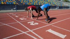 Los atletas multirraciales en la posición de salida, alistan para correr después del comando, maratón imagenes de archivo