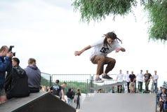 Los atletas tienen una competencia amistosa del monopatín en Gomel Fragmento de un skater, que hace salto Imágenes de archivo libres de regalías