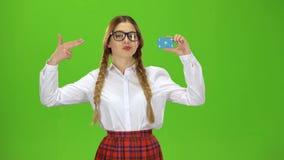 Los aumentos adolescentes una tarjeta y los puntos en ella, ella sonríe Pantalla verde metrajes