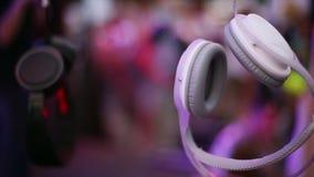 Los auriculares blancos y negros cuelgan en el alambre en el partido del festival del aire abierto hospitalidad Gente holidays metrajes