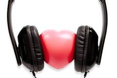 Los auriculares del concepto con el corazón Imágenes de archivo libres de regalías