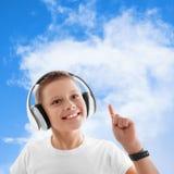 Los auriculares del muchacho del niño del cielo de las nubes de la música escuchan Fotos de archivo libres de regalías