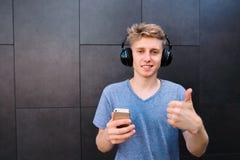 Los auriculares inwireless del adolescente y con el teléfono en sus manos muestran un finger para arriba contra la perspectiva de Imágenes de archivo libres de regalías