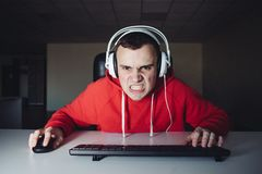 Los auriculares malvados del videojugador del retrato que miran cuidadosamente supervisan su ordenador y los videojuegos el jugar imagenes de archivo