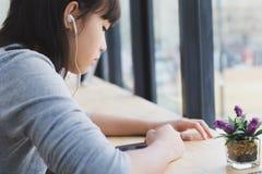 los auriculares que llevan de la muchacha del estudiante femenino asiático del adolescente y escuchan Foto de archivo