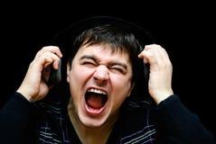 Los auriculares que llevan del hombre de pelo oscuro, el suyo boca abierta de par en par cantan Imagen de archivo