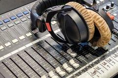 Los auriculares se colocan en el regulador audio en sitio de la grabación Imagenes de archivo