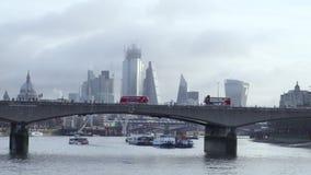 Los autobuses de Londres cruzan el horizonte de la ciudad en el amanecer almacen de video