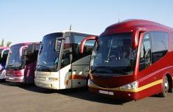 Los autobuses o los coches parquearon en un aparcamiento Imagen de archivo libre de regalías
