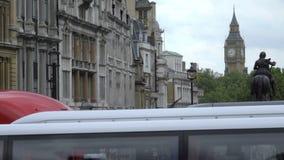 Los autobuses pasan por Big Ben y la estatua de George IV metrajes